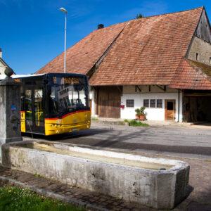 Ein Postauto im historischen Dorfkern von Möhlin