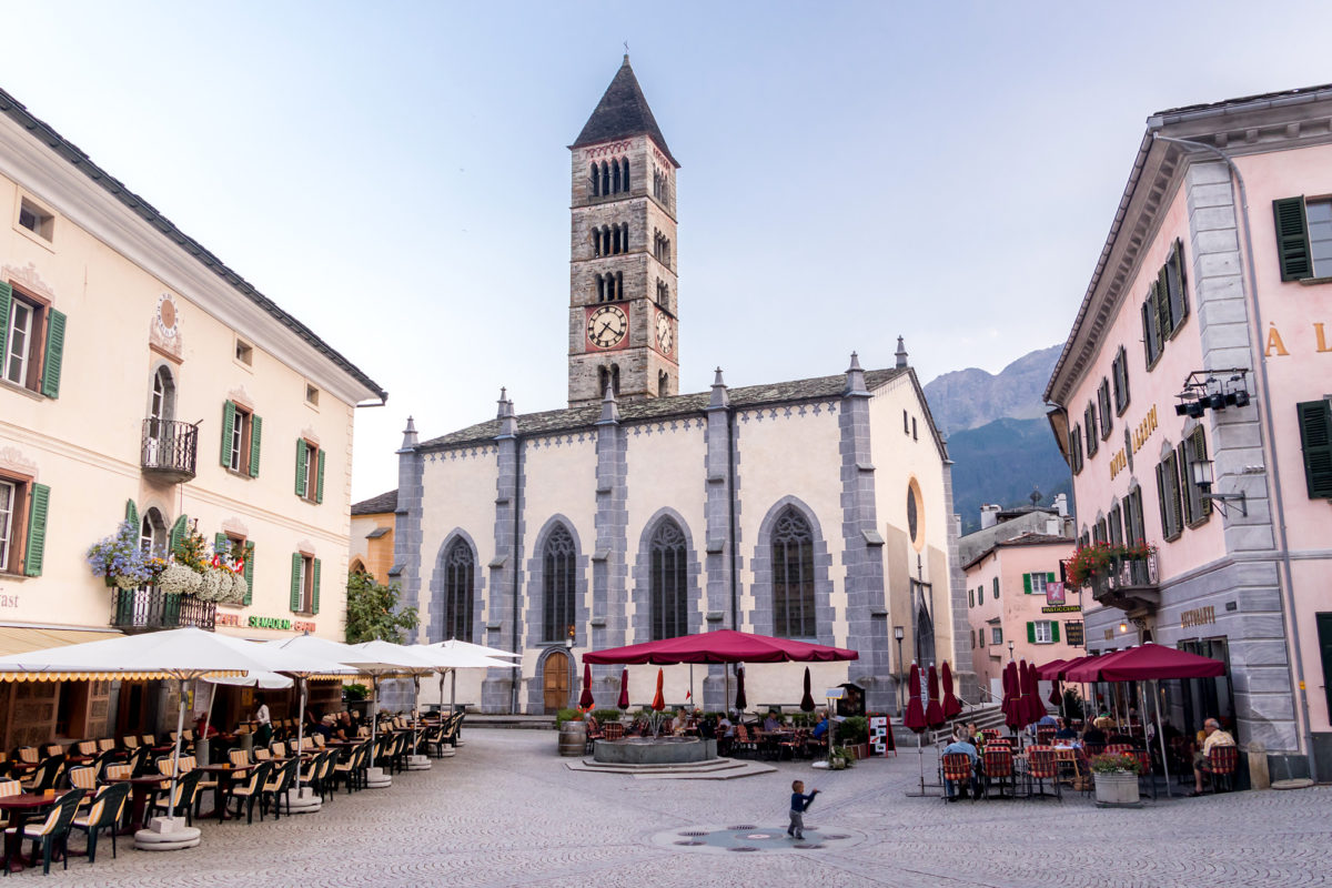 An der Piazza von Poschiavo. Im Hintergrund die Stiftskirche San Vittore mit ihrem romanischen Turm aus dem 13. Jahrhundert.