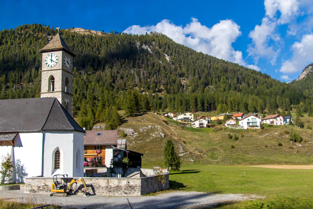 Tschierv (im Hintergrund), davor die reformierte Kirche des Dorfes, erbaut 1470