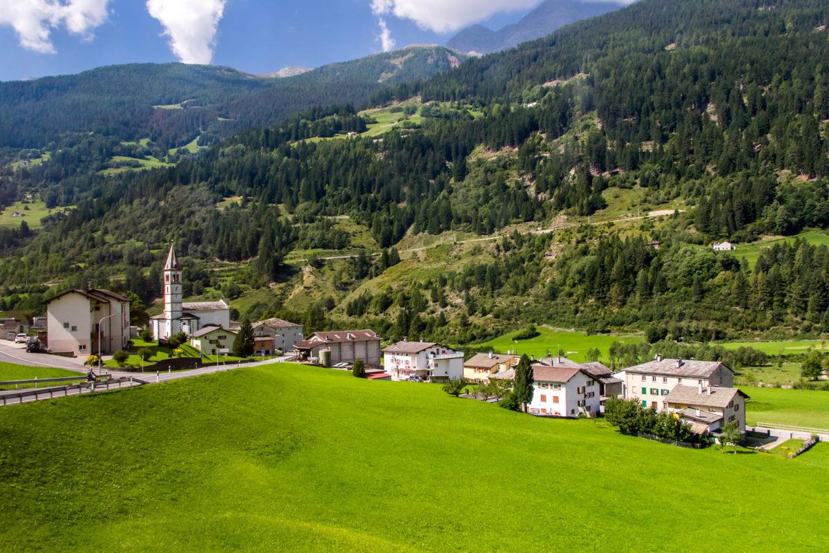 San Carlo, ein Weiler von Poschiavo. Im Hintergrund ist die ansteigende Bernina-Strecke sichtbar.