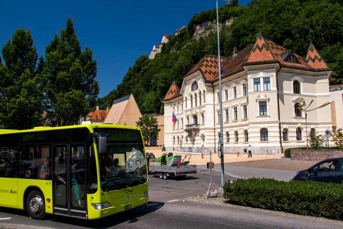 Trotz grüner Farbe: Auch in Liechtenstein sind Postautos unterwegs, hier im Zentrum von Vaduz mit Regierungsgebäude und dem Schloss des Fürsten (oben)
