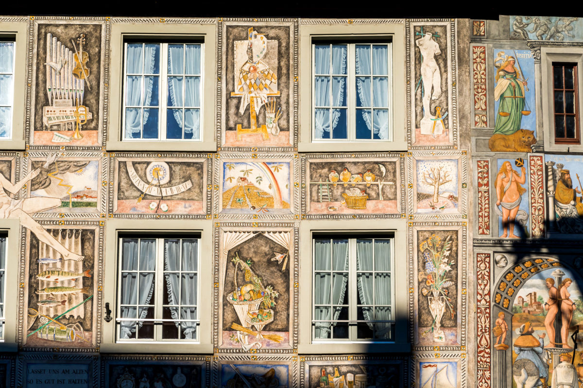 """Die prächtige Fassade am Hotel/Restaurant Adler ist als einzige des Städtchens neueren Ursprungs: Sie wurde 1956 von Alois Carigiet geschaffen - genau demjenigen, welcher auch das berühmte Buch """"Schellenursli"""" geschrieben hat. Die Motive zur Rechten stammen allerdings aus dem 16. Jahrhundert."""