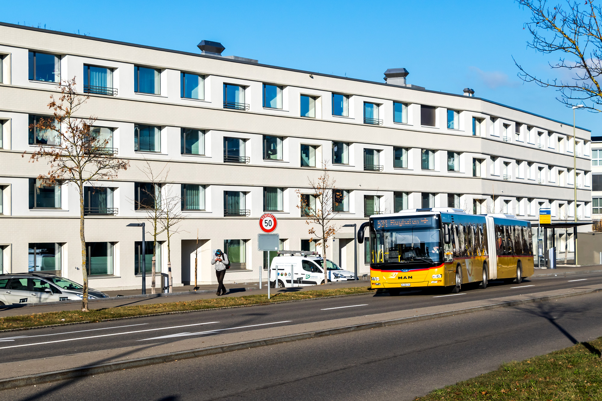 Agglomerations-Express: Das Postauto vor einem besonders monotonen Wohnblock eingangs Bülach